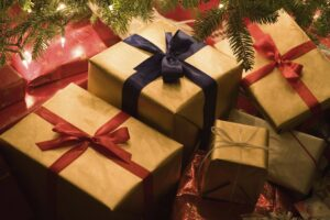 Christmas presents piled underneath a christmas tree.